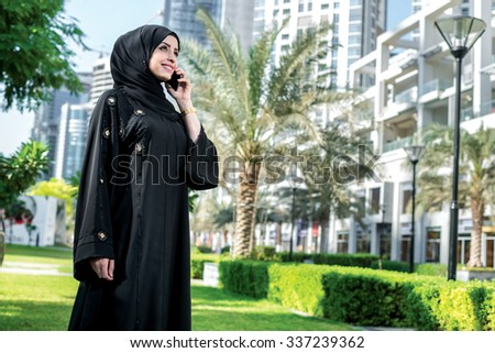 Happy talk on a cell phone. Arab businesswoman wearing hijab holding cell phone against the backdrop of skyscrapers in Dubai and looking at cell phone. The woman is dressed in a black abaya - stock photo