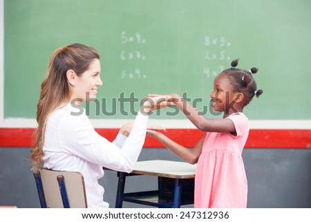 Happy teacher and afroamerican elementary student congratulating during math lesson. - stock photo