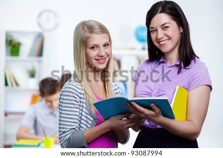 Happy teacher and her student looking at camera in college