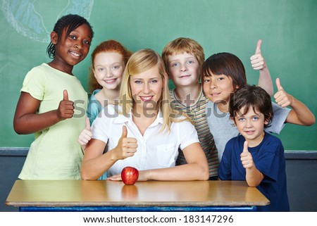 Happy teacher and smiling elementary school students holding thumbs up - stock photo