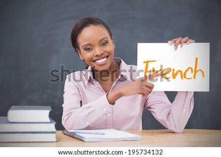 Happy teacher holding page showing french in her classroom at school - stock photo