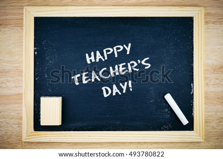 Happy Teacher's Day.. Blackboard with Happy Teacher's Day sign, white chalk and duster on wooden background