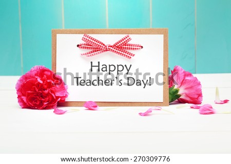 Happy Teachers Day card with pink carnations over teal wooden wall - stock photo