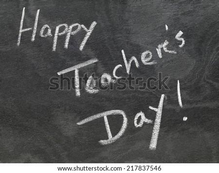Happy Teachers Day written in chalkboard with white chalk - stock photo