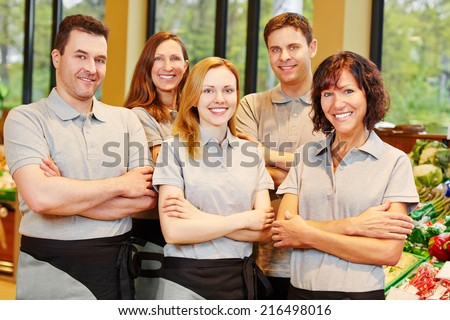 Happy team of smiling men and women staff in a supermarket - stock photo