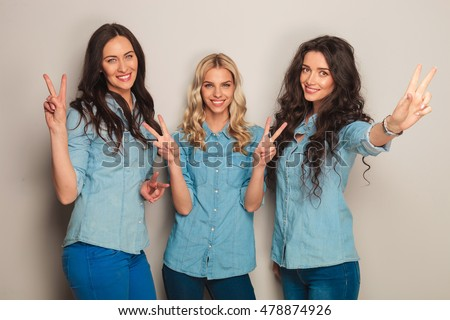 happy team of three casual women showing the victory sign in studio on grey background
