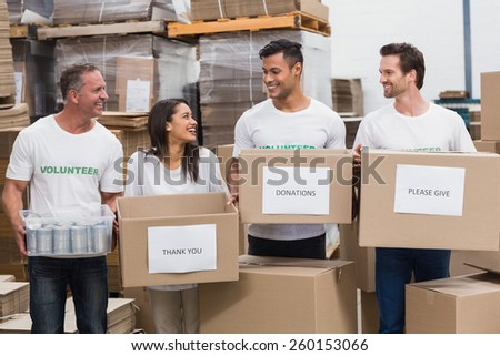 Happy team of volunteers holding donations boxes in a large warehouse - stock photo