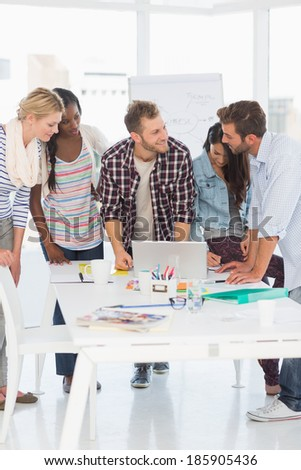 Happy team of young designers having a meeting in creative office - stock photo