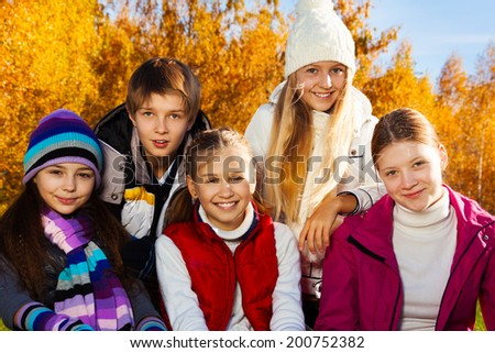 Happy teen age kids, group of five girls and a boy together in close shoot in the park on sunny autumn day. - stock photo