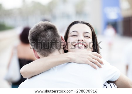 Happy teen couple embracing at street. Love concept
