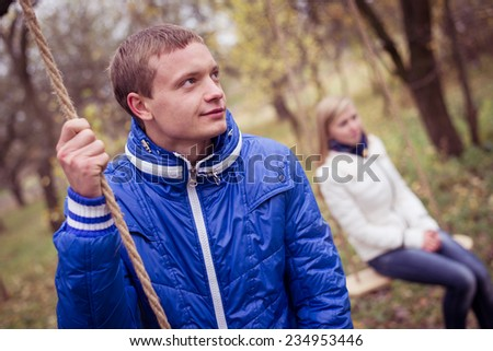 Happy teen couple outdoors on cold autumn day sitting on swings - stock photo
