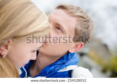 Happy teen couple walking outdoors on cold autumn day - stock photo