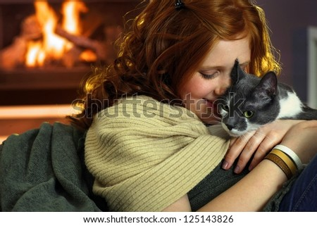 Happy teen girl caressing cat at home, affectionate moment. - stock photo