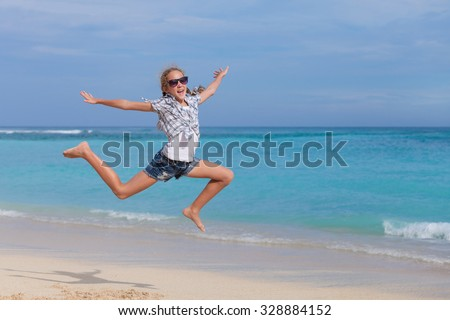 Happy teen girl  jumping on the beach at the day time - stock photo
