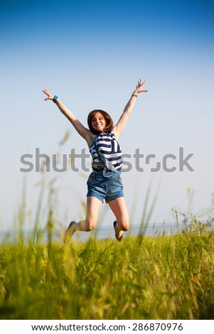 Happy teen girl jumping over blue sky. Beauty girl having fun outdoor. Freedom concept.
