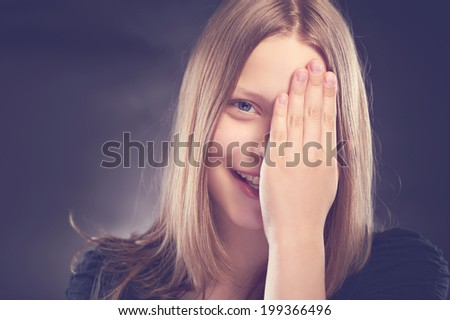 Happy teen girl laughing and hides her face behind her hand - stock photo