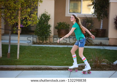 Happy teen girl roller skating in front of her house