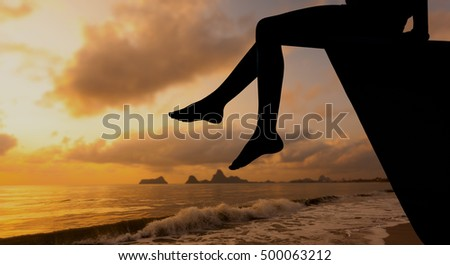 happy teen girl sitting on beach at the dawn time. Concept of life.