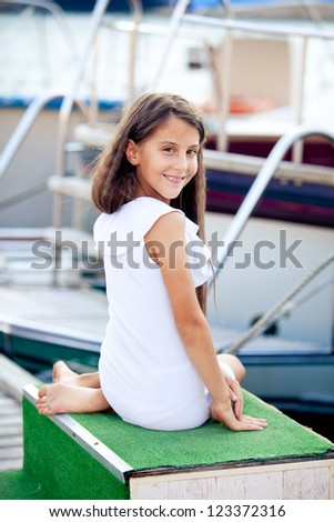 Happy teen girl sitting on berth in summer