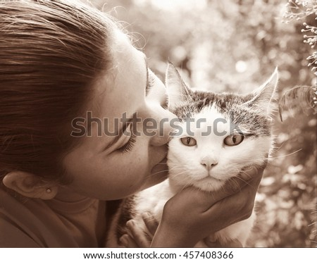 happy teen girl with cat close up sepia black and white portrait on the summer garden background - stock photo