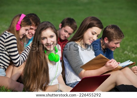 Happy teen girl with friends studying outdoors - stock photo