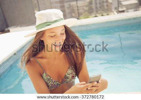 Happy teen girl with mobile phone in swimming pool - stock photo