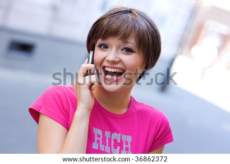 happy teen girl with mobile phone on the street - stock photo