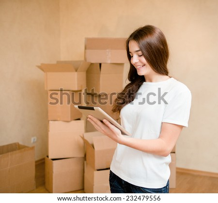 happy teen girl with tablet computer standing on a background of cardboard boxes.