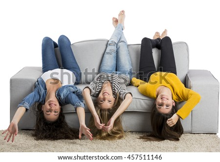 Happy teen girls at home sitting on the couch