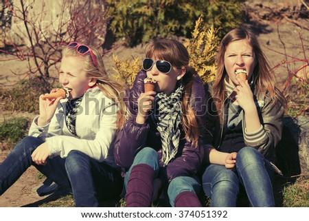 Happy teen girls eating an ice cream outdoor - stock photo
