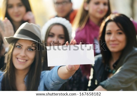 Happy teen girls having good fun time outdoors with banner paper for copy space - stock photo