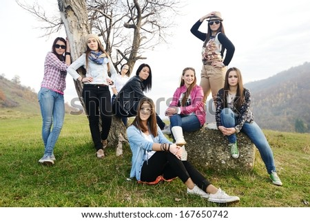 Happy teen girls having good fun time sitting on green meadow