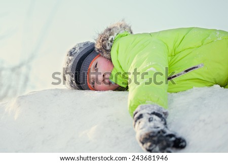 Happy teen in winter wear smiling while playing in snowdrift outside - stock photo