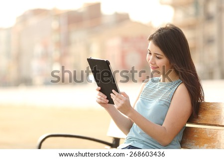 Happy teen student girl reading a tablet or ebook and learning in a park - stock photo