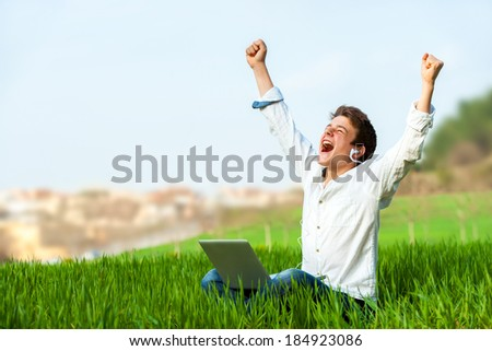 Happy teen with laptop in green field shouting of joy. - stock photo
