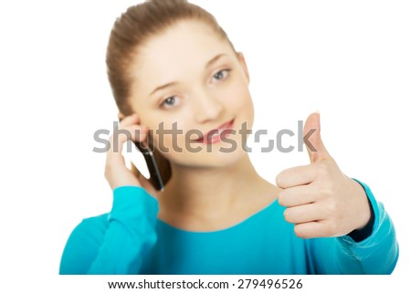 Happy teen with mobile phone and thumbs up. - stock photo