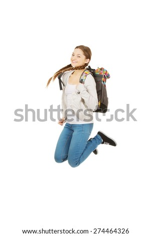 Happy teen woman jumping with backpack. - stock photo