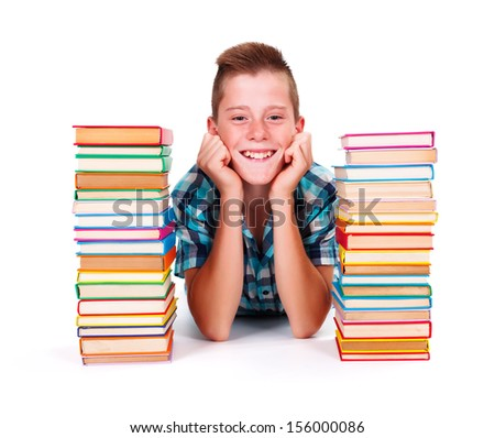 Happy teenage boy between tower of books smiling