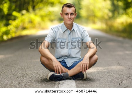 Happy teenage boy smiling relaxed while sitting in the middle of an empty road