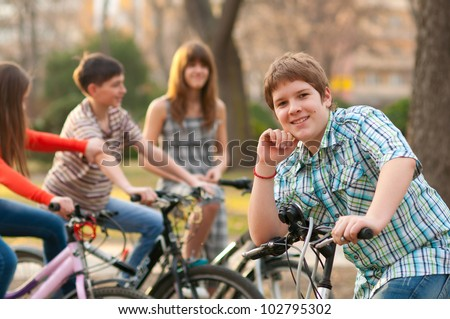 Happy teenage boy spending time with his friends riding bicycles. - stock photo
