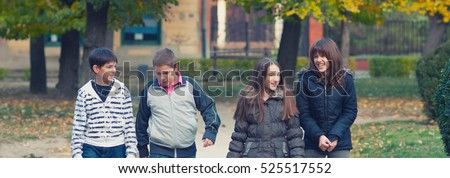 Happy teenage boys and girl having fun and walking in the autumn park