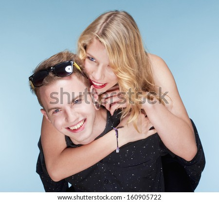happy teenage couple piggybacking, smiling - isolated on blue. - stock photo