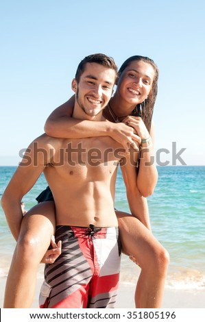 Happy teenage couple playing at the beach