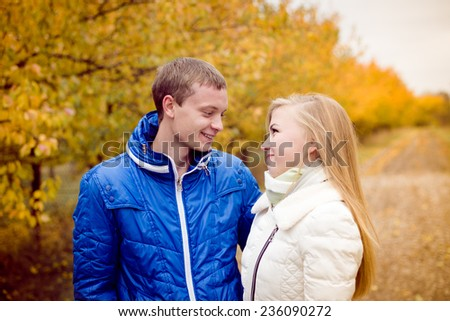 Happy teenage couple walking outdoors on cold autumn day - stock photo