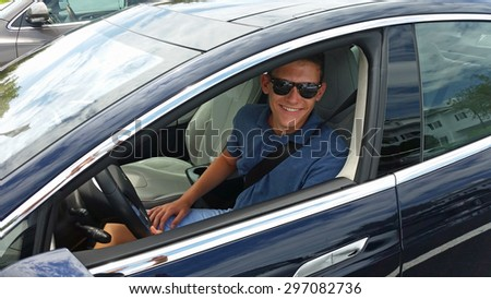 Happy teenage driver in a new Tesla electric car - stock photo