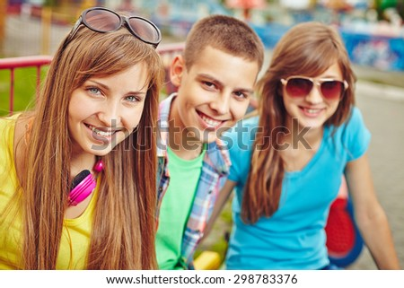 Happy teenage friends looking at camera outdoors - stock photo