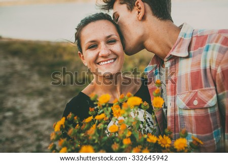 Happy teenage girl being kissed by her boyfriend outdoors. Happy relationship. Lifestyle. Feelings. Love. - stock photo