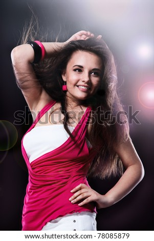 Happy teenage girl dancing, over black