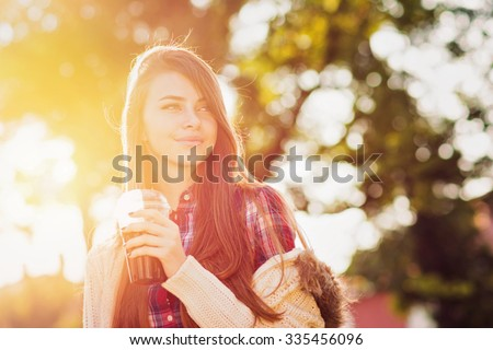 Happy teenage girl in autumn in park holding takeaway coffee. Beautiful young woman with coffee outdoors on sunny fall day. Vibrant colors, back light, shallow depth of field, medium retouch. - stock photo