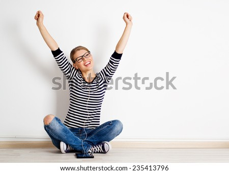 Happy teenage girl in casual clothes with digital tablet listening music in headphones. Carefree lifestyle concept.  - stock photo